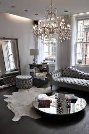 a silver grey living room with a large crystal chandelier with candle inspired bulbs