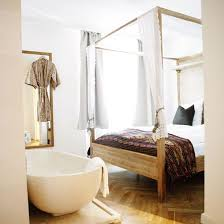a boho girlish bedroom with a free standing bathtub next to the bed for adding