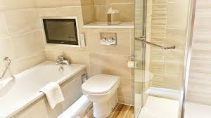 cottons hotel spa bathroom with a tv tub and wet room with overhead