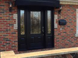 exterior black wooden door with frosted glass insert narrow window sidelights and false exposed brick wall with mounted lamp exterior ideas