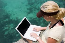 woman working on a laptop by the ocean marine biologist job description and salary