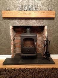interior brick stone fireplace with black metal fire box and brown wooden storage on patterned
