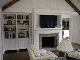 built in window seat bookcase around fireplace in family room with tv mounted above fireplace