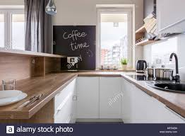 Kitchen With Wooden Countertop White Cabinets And Chalkboard Stock