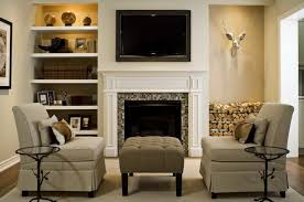 lovely living room with grasscloth lined nooks flanking fireplace with mosaic glass tiles tv white floating shelves stacked firewood oatmeal linen