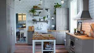 black cabinet pulls on gray cabinets. white tile wall, light gray cabinets, kitchen island, wood floors, ceramic knob with black pattern cabinet pulls on cabinets e