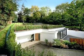 house plans built into a hill underground tucked away under a grassy hill at first glance