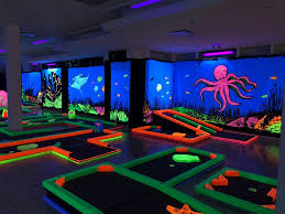 special florescent golf putters course obstacles and wall décor all glow under black lights