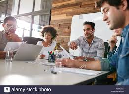 office meeting. Multiracial Group Of Business People Meeting In Modern Office. Team Holding Plan Discussing About Progress Project. Office