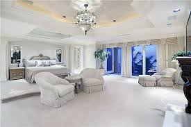 luxury bedroom with elevated bed platform tray ceiling chandelier and balcony