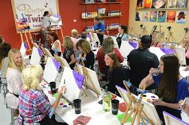 painters start their canvases and sip wine during class at painting with a twist