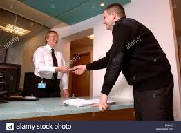 a security guard on patrol signs in at a front desk with another security officer at a business premises uk