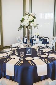 Tall white floral arrangement with silver accents and blue linens. #NC # wedding #