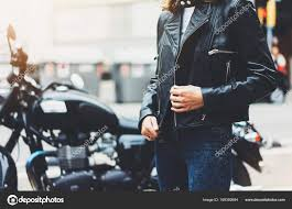 girl unfastens black leather jacket on background motorcycle in sun flare atmospheric city hipster biker female hands closeup motorbike street lifestyle