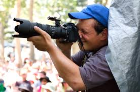 A photographer tacking a picture with a large SLR lens