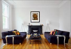 dark blue fabric cover double sleeper sofa and rectangle coffee table on wooden floor also black fireplace idea