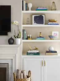 welcoming living room features styled white built in shelves fixed above white cabinets and beside a modern white marble fireplace with a white mantle