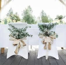 wedding chairs decorated with flowers and hessian