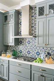 bold navy and white moroccan patterned tiles add visual interest to the grey cabinets