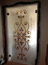 large twin folding frosted glass door with golden curving ornaments placed on the brown wall