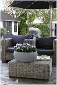 for upstairs balcony: garden 'lounge' with palest wicker furniture, grey  cushions and umbrella with a large stone bowl filled with pansies