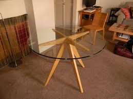 furniture round glass top dining table with three brown wooden bases on brown carpet