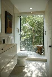 beige bathroom floating cabinets low seat toilet floor to ceiling windows glass shower modern painting
