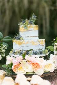 Gold And White Wedding Cake Topped With Berries Brides