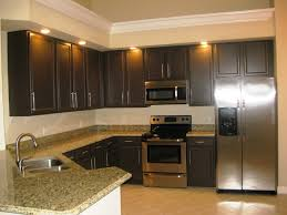 kitchen dark brown wooden cabinet with cream marble counter top plus silver stove placed on