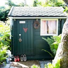 the garden shed looks so pretty with its tiled roof dark green painted wood and cottage style window