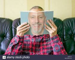 a man reading a book about himself with his face seen on the cover