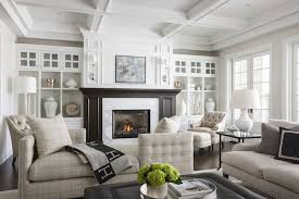 lovely living room features a coffered ceiling over dark stained fireplace mantle accented with marble surround under abstract art illuminated by french