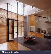 Kitchen Granite Worktops Wooden Venetian Blinds On Glass Doors In Large Double Height