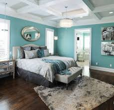 turquoise bedroom with a round mirror above bed