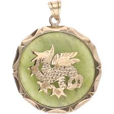 14 kt yellow gold pendant set with a jade with a yellow gold dragon on