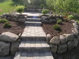 custom build brick paver steps and paver walkway leading to outdoor wood burning firepit surrounded by blooming plants in raised boulder planters