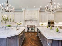 beautiful kitchen with white cabinets two islands two chandeliers and carrara marble countertops