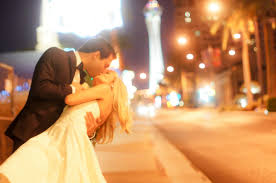groom dips his bride for a kiss outside on the las vegas strip in fron of