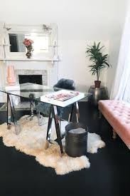 black and white office decor. feminine minimalist office decor chic west elm glass desk on a white fur rug wayfair pink tufted bench black wood floors and bright walls