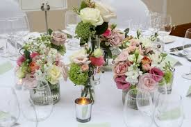 round top table wedding flowers with cers of jars and small milk bottles