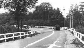 an old photograph of a bend in a road surrounded by trees and power poles