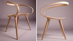 the back of this sleek dining chair is made from a single piece of bent wood giving it a smooth seamless look