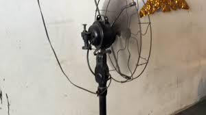 ge brand antique or replica pedestal stand fan in a market