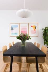 minimalist dining room with a colorful trio of artwork