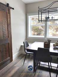 benjamin moore baby fawn in dining room wtih farmhouse style sliding barn door and metal chandelier