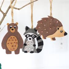 small felt ornaments hanging from a branch as woodland baby shower decorations including a bear