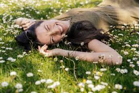 Happy woman enjoying her free time while lying on grass with daisies - MFF05707 - Mareen Fischinger/Westend61