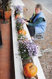 Donna Barton arranges an autumn tableau on the porch of the Blue Moon Café  in Stowe village on Tuesday. | News | vtcng.com