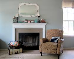 charming white painted fireplace mantel also white mirror frames hang on grey wall as well as brown accent chairs in modern living areas designs