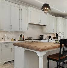 Country kitchen design shown includes a center island built of Shaker  cabinets with decorate end panels